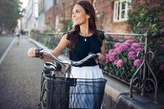 有自行车的微笑的妇女步行沿着向下街道的 免版税库存照片