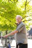 有自行车的愉快和微笑的年长人 免版税库存图片