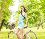 有自行车的愉快的可爱的女孩 免版税图库摄影