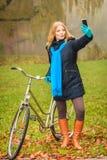 有自行车的愉快的妇女在拍selfie照片的公园 库存照片