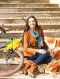 有自行车的愉快的妇女在秋天公园 库存照片