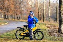 有自行车的愉快的小男孩在秋天公园 免版税库存照片