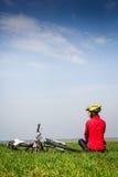 有自行车的愉快的活跃女孩享受在一个绿色草甸的看法 免版税库存图片