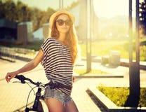 有自行车的时髦行家女孩在城市 免版税库存图片