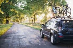 有自行车的汽车在森林公路 免版税图库摄影