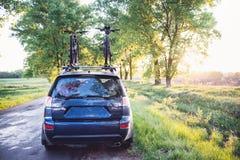 有自行车的汽车在森林公路 免版税库存图片