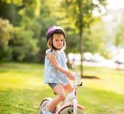 有自行车的生气的女婴在公园 免版税库存照片