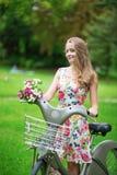 有自行车的美丽的女孩在乡下 免版税库存图片
