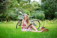 有自行车的美丽的女孩,读书 免版税库存图片