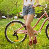 有自行车的美丽的妇女在公园 库存照片