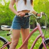 有自行车的美丽的妇女在公园 免版税库存照片