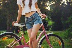有自行车的美丽的妇女在公园 库存图片