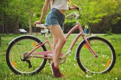 有自行车的美丽的妇女在公园 免版税库存图片