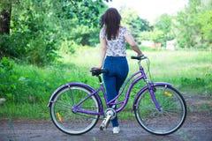 有自行车的美丽的妇女在城市公园 美好的本质 库存图片