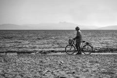 有自行车的老人单独走在Rafina沙子海滩的  希腊 免版税图库摄影