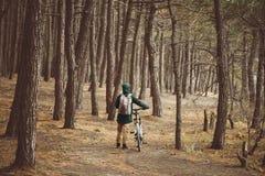 有自行车的远足者妇女在森林里 库存照片