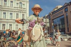 有自行车的逗人喜爱的妇女和teddybear去葡萄酒节日在欧洲 免版税图库摄影