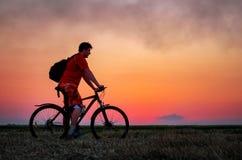 有自行车的骑自行车的人在日出的领域 库存照片