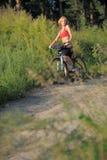 有自行车的年轻美丽的妇女在小山的上面 免版税库存照片