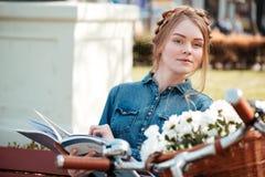 有自行车读书杂志的美丽的妇女在户外长凳 库存图片