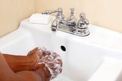 有色人在水槽的洗涤的手 免版税库存图片