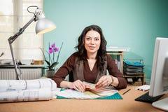 有色板显示的微笑的建筑师在她的书桌上 免版税库存图片