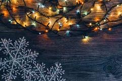 有色的光和雪花的诗歌选在木背景 抽象空白背景圣诞节黑暗的装饰设计模式红色的星形 库存图片