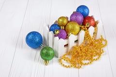 有色的圣诞树球和金黄小珠的白色箱子装饰的 库存照片