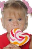 有色的棒棒糖的小美丽的女孩 免版税库存图片