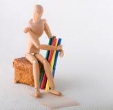 有色的毡尖的笔的木玩偶在一个柳条小箱 图库摄影