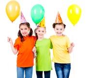 有色的气球的三个逗人喜爱的小女孩 免版税库存照片