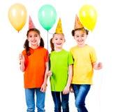 有色的气球的三个逗人喜爱的小女孩 库存图片