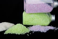 有色的海盐和堆的透明瓶水晶 免版税库存图片