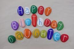 有色的石头的生日快乐女儿在白色沙子 免版税图库摄影