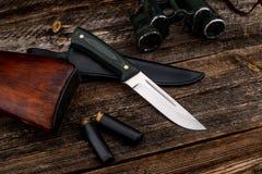 有色的碳把柄的纯金属刀子在自然木板条背景的 库存照片