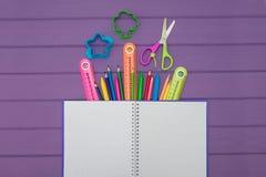 有色的铅笔、统治者和剪刀的一个笔记本 免版税库存照片