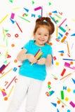 有色的铅笔的愉快的小女孩在她的手 图库摄影