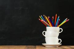 有色的铅笔的被堆积的咖啡杯 库存图片