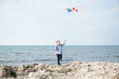 有色的风筝的愉快的令人愉快的小男孩由海 图库摄影