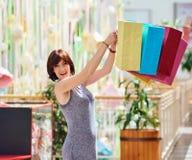 有色的购物袋的成熟愉快的妇女 免版税库存照片