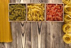 有色的fusilli的三个木箱在木背景在意粉和tagliatelle旁边 库存图片