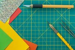 有艺术刀子、镊子和纸工艺的绿色切口席子 免版税库存图片