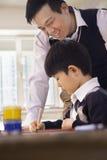 有艺术和工艺的,北京老师帮助的男小学生 图库摄影