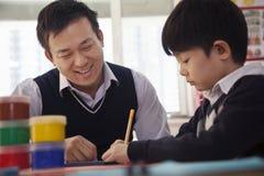 有艺术和工艺的,北京老师帮助的男小学生 库存图片
