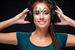 有艺术构成的现代少妇喜欢听到在耳机的音乐 正面情感,休闲 复制空间 库存图片