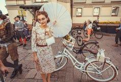 有节日的大夏天伞和葡萄酒自行车等待的开始的少妇 免版税库存照片
