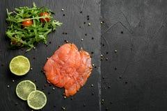 有芝麻菜和柠檬的新鲜的被切的三文鱼内圆角在板岩板材,顶视图 库存图片