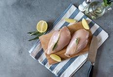 有芝麻菜的未加工的鸡内圆角在切板和毛巾、刀子、油瓶和盐瓶在灰色背景 免版税库存图片