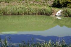 有芦苇和一条木小船的湖在岸 免版税库存图片