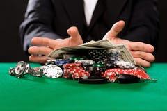 有芯片的打牌者和金钱在赌博娱乐场桌上 免版税库存照片